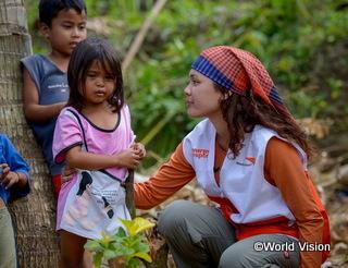 2013年フィリピンを直撃した大型台風で被災した子どもの声に耳を傾けるスタッフ