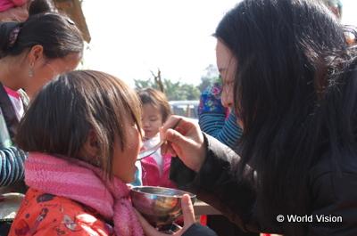 保健クラブに参加しに来ていた子どもにおかゆを冷まして与える三浦スタッフ2