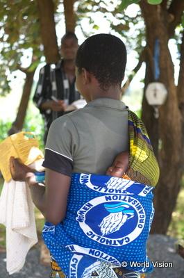 子どもの健診のためにヘルスセンターを訪れた親子。手に持っているのは母子手帳(ンチシ県母子保健関連施設整備事業)