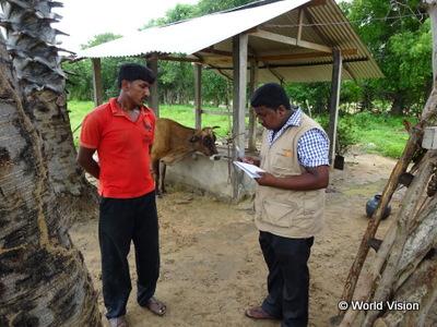 住民(写真左)と話す事業スタッフ(スリランカ国キリノッチ県における小規模畜産農家の家畜生産性向上プロジェクト)