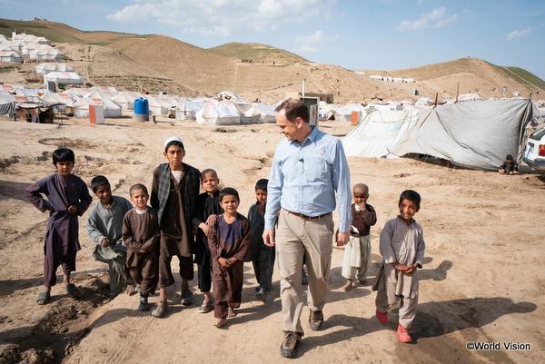 ワールド・ビジョンのスタッフと難民キャンプで生活している子どもたち