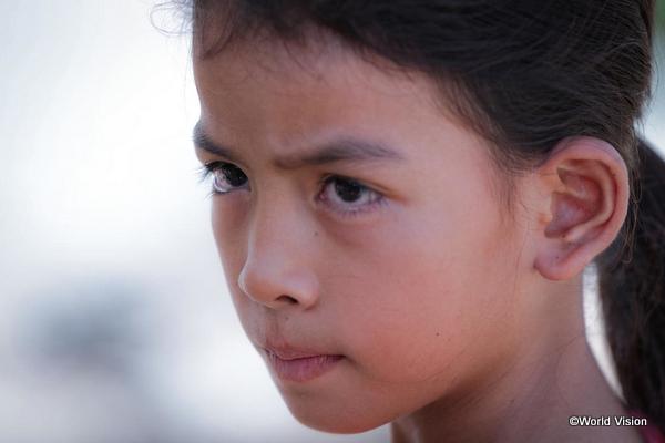 鋭い表情で遠くを見るカンボジアの子ども
