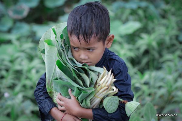 葉を抱えながら悲しい顔をするカンボジアの子ども