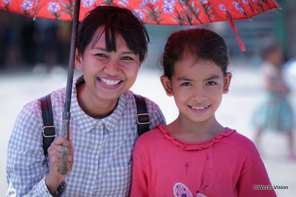笑顔でこちらを見るカンボジアの女性と子ども