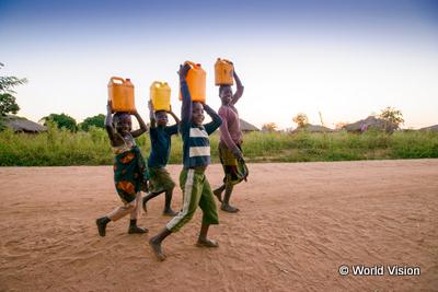 水が入った重いタンクを頭にのせて歩く子どもたち写真