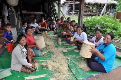 家族の収入を増やすための生計向上プログラム。20人の女性が集まりかご作りをしています。かごを売って現金収入を得て、子どもたちに栄養のある食べ物を買うことができるようになってきています(カンボジア)