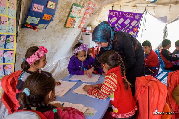 シリア難民の子どもたちに教育プログラムを実施するワールド・ビジョンのスタッフ