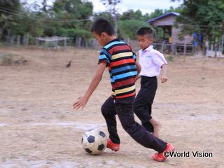 休み時間に友だちとサッカーをするポウイ君(右)