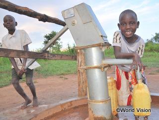 井戸で水汲みのお手伝いをするジェーンちゃん(右)