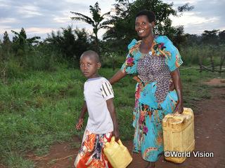 汲んだ水を運ぶジェーンちゃんと母親のベアトリスさん