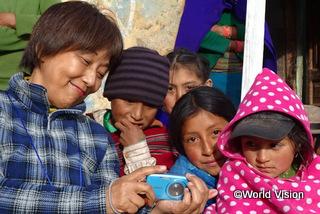 撮った写真を子どもたちと一緒に見ている様子 (2014年エクアドルツアー)