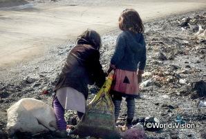 アフガニスタンの子どもが路上のごみを集めている。
