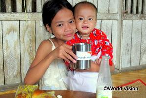 ミャンマーの兄弟がワールド・ビジョンのロゴの入ったカップで牛乳を飲んでいる