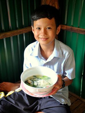 カンボジアの男の子がスープの入った器を持って笑っている