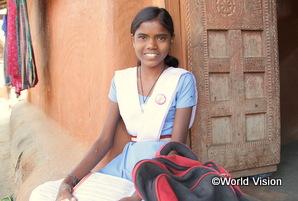 インドの女の子が教科書を持って笑顔を浮かべている