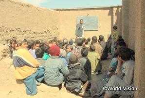アフガニスタンの男の子たちが屋根のない教室で授業を受けている