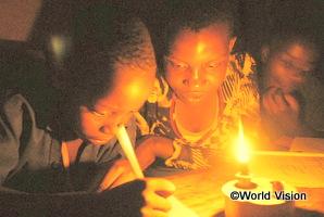 ルワンダの兄妹が支援でもらったランプの明かりで勉強している