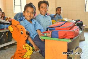 インドの男の子が新しい机に座って笑っている