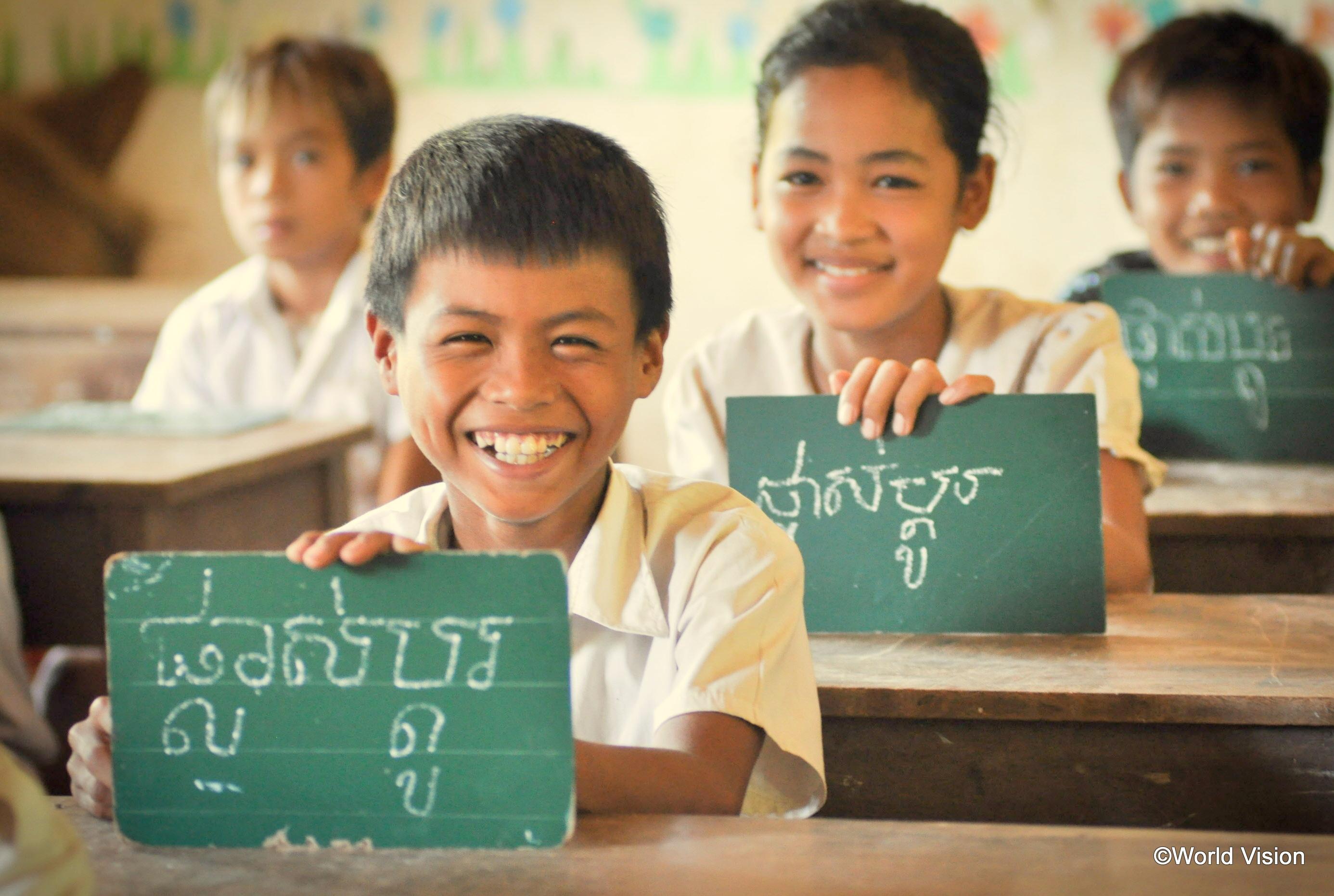 カンボジアの男の子が教室で黒板に文字を書いて満面の笑み