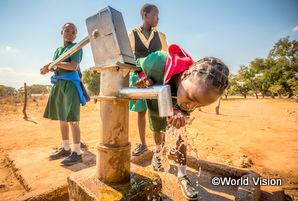 ザンビアの女の子がポンプで汲んだきれいな水を飲んでいる