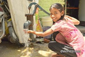 インドの女の子がポンプで水を汲んで笑っている