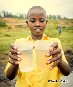 ルワンダの男の子が濁った水と透き通った水をコップに入れて比べている