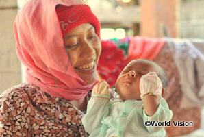 カンボジアの母親が生まれたばかりの子どもを抱きかかえている