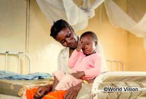 ザンビアの男の子が母親と病院で順番を待っている