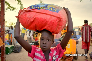ケニアの難民の子どもが大きな袋を頭の上に乗せている