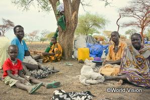 南スーダンの難民の家族が生活している木の下に座っている