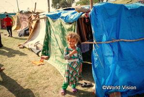 シリアからイラクに逃げてきた女の子が難民キャンプの家の前でたたずんでいる
