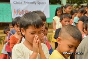 フィリピンの台風で被災した地域の男の子が祈っている