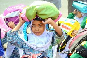 インドネシアの女の子が頭にバッグを乗せて避難訓練