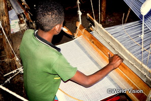 エチオピアの男の子が機織り機を使って働いている
