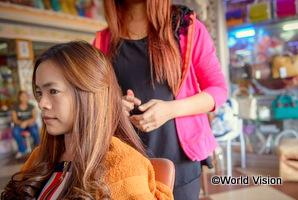 過去に人身売買の被害を受けたカンボジアの女性が美容師の資格を取って仕事をしている