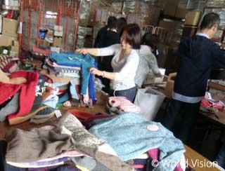 全国のボランティアから送られた編み物をサイズごとに仕分けする様子