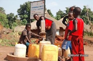 南スーダンの難民キャンプで、支援によって設置された井戸を使って水汲みをする子どもたち。