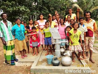 ご寄付により完成した井戸の前で喜ぶ子どもたち