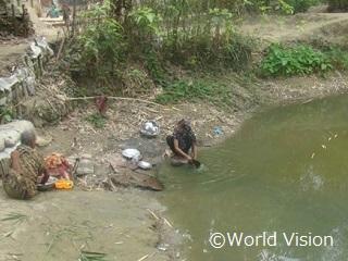 水溜りの水を生活用水として使用する女性たち