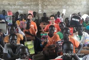 学用品を手に喜ぶ南スーダン難民の子どもたちと村松スタッフ(中央右)・大井スタッフ(中央左)