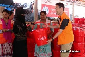 ミャンマーから逃れてきたロヒンギャ難民の女性に支援キットを渡す平本スタッフ(バングラデシュ))