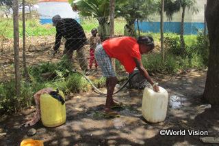 【キアムボゴコ地域】「以前は、水を汲むために長い列を作って待たなければなりませんでした。今は、近くで清潔な水を手に入れることができるので、ほかの仕事をする時間ができました。」 チェベットさん(地域の母親、赤いシャツの女性)