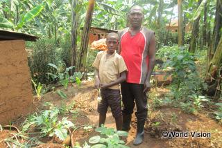 【グウィザ地域】「家庭菜園を始めてから、子どもたちに食事を与えるのが以前よりずっと楽になりました。収穫の一部を売ったお金は、学用品や授業料に充てています。」 家庭菜園の前に立つジェームズさん