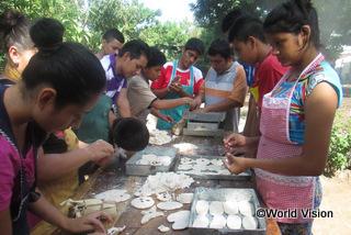 【サンアグスティン地域】「パン焼きの講習会は将来の助けになると思います。パンを焼いてお金を稼ぐことができるからです。ぼくはほかにビジネスについての話し合いにも参加しました。」 ペドロ君(赤いシャツとエプロンを着た中央の若者)