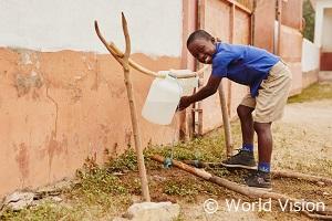 簡易水道で手を洗う支援地域の男の子