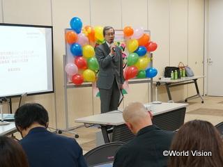 事業説明会で挨拶するWVJ事務局長の片山