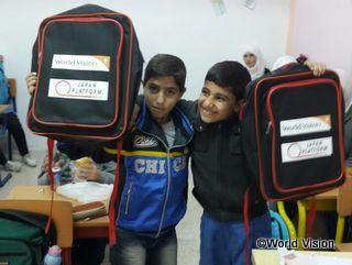 支援で届けられたバッグを手に笑顔を見せる子どもたち