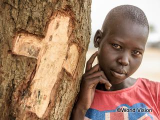 十字架が刻まれた木に寄りかかるニャメールちゃん