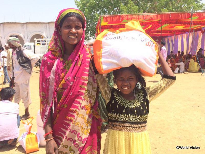 食糧等の支援物資を受け取り、安堵した表情の母子。2016年、この地域は深刻な干ばつに見舞われました(インド)