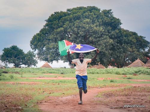 南スーダン国旗を掲げて走るアプクさん